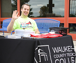 WCTC student at table welcoming new students during welcome week